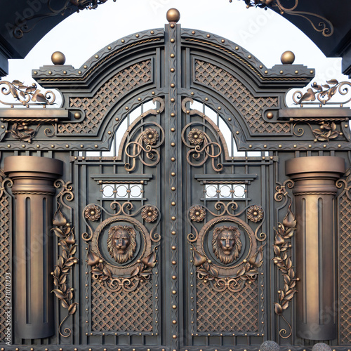 Fotografia New forged metal massive gates with a wicket and two arches, golden gray, made in antiquity