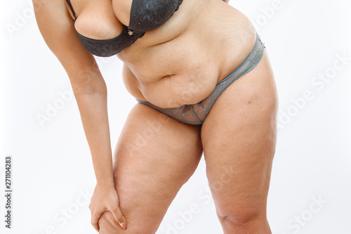 Wallpaper Mural young overweighted woman in lingerie on white isolated background squeezes fat on legs