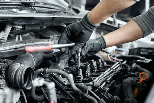 Billede på lærred Close up of man's hands using wrench to remove spark plugs