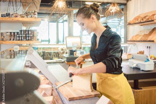 Junge Verkäuferin in Feinkostladen schneidet Käse Fototapete