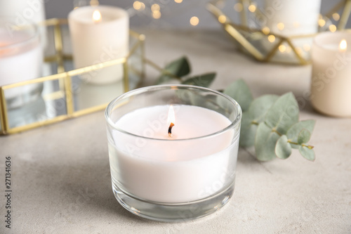 Canvas Print Burning aromatic candle and eucalyptus branch on table