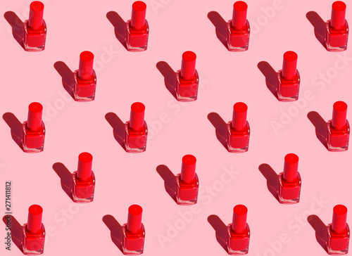 Photo Pattern from red nail polish bottles arranged in symmetrical geometric rows on fuchsia pink background