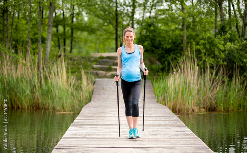 Obraz na płótnie Pregnant woman nordic walking outdoor, exercises during pregnancy