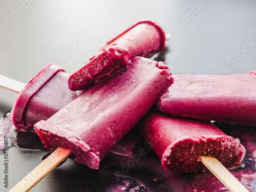 Fotografija Bright, fruity fuchsia ice cream with wooden sticks on a dark surface