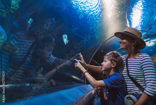 Fotografie, Tablou Mother and son walking in indoor huge aquarium tunnel, enjoying a underwater sea inhabitants, showing an interesting to each other