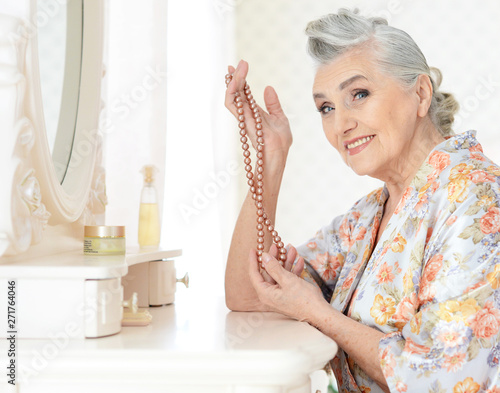 Portrait of happy senior woman sitting near dressing table Fototapete