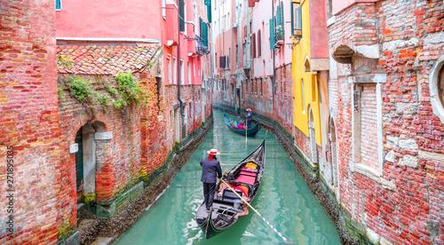 Obraz na płótnie Venetian gondolier punting gondola through green canal waters of Venice Italy
