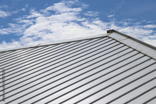 Fotografía Metal sheet roof and slope with clouds and blue sky background.