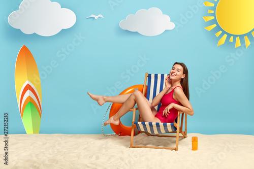 Obraz na płótnie Slim good looking female rests in deckchair at beach, shows slender legs, wears