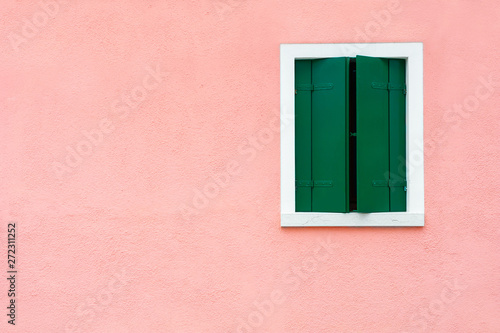Window with green shutters on the pink wall. Colorful architecture in Burano island, Venice, Italy.