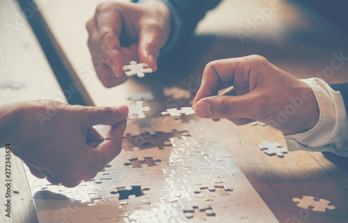 Implement improve puzzle solve connections together with synergy strategy team building organizing connection by trust communication. Hands of stakeholders business trust team holding jigsaw puzzle