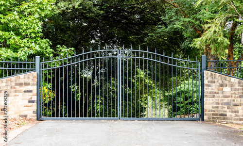 Foto Metal driveway property entrance gates set in brick fence with garden trees  in