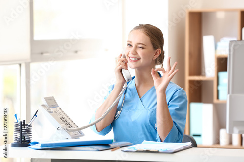 Fotografia Young medical assistant talking by phone in clinic