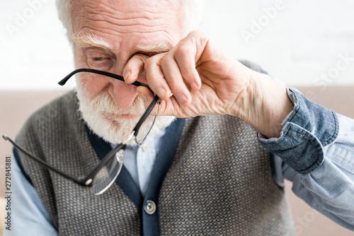 Fotografia Sad senior man holding glasses, and covering eye of his hand