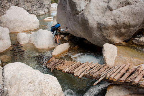 Canvas-taulu Female hiker wades through river between cliffs