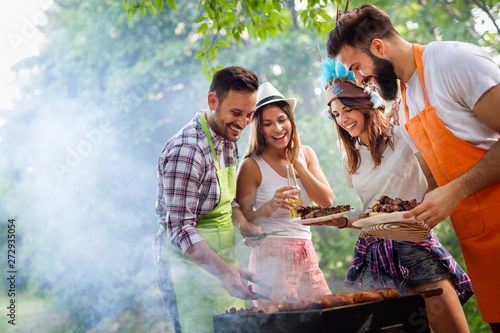 Friends making barbecue and having lunch in the nature Fotobehang