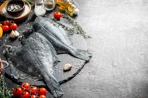 Fotografiet Raw flounder with cherry tomatoes, spices and garlic cloves.