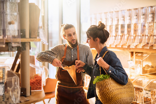 Foto Beautiful young woman shopping in a bulk food store