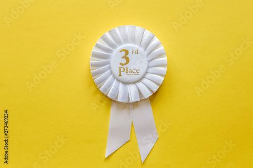 Obraz na płótnie 3rd place white ribbon rosette on yellow