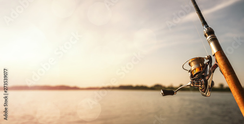 Fotomural Close up of a fishing rod during the sunset with copy space