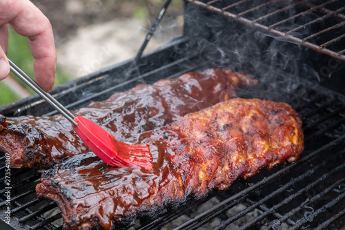 Fotografie, Obraz Pork ribs cooking on barbecue grill for summer outdoor party.
