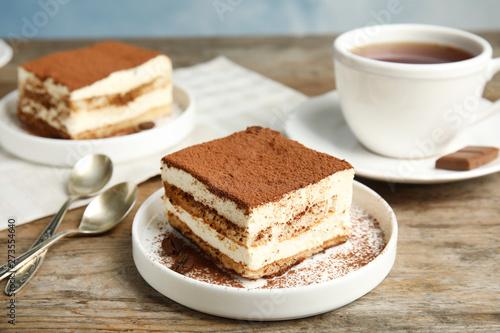 Fototapeta Composition with tiramisu cakes and tea on table