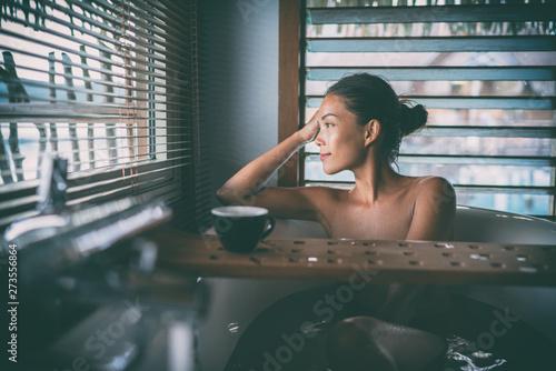 Luxury bath Asian woman relaxing in warm water enjoying view from bathroom window lying in bathtub with bath wooden board caddy drinking coffee cup Fototapeta