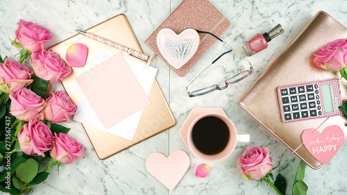 Ultra feminine pink desk workspace with rose gold accessories on white marble background flatlay overhead.