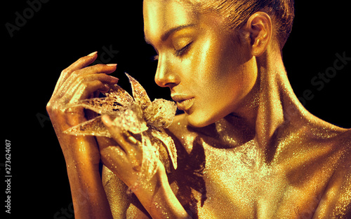 Fashion model woman with bright golden sparkles on skin posing, fantasy flower. Portrait of beautiful girl with glowing makeup. Art design gold sequins make up. Glitter glowing golden skin