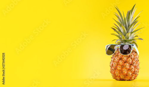 Fotografia Creative pineapple looking up with sunglasses and shell isolated on yellow backg