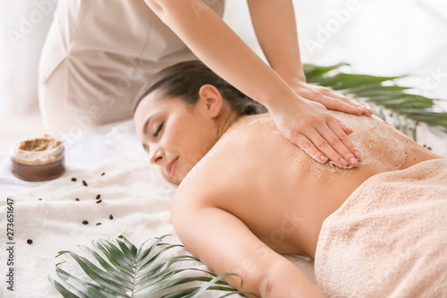 Foto Young woman undergoing treatment with body scrub in spa salon