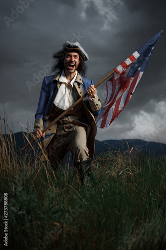 Canvas Print American revolution war soldier with flag of colonies over dramatic landscape
