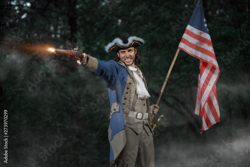 Foto Epic Portrait of man dressed as soldier of american revolution war of United States aims from pistol with flag