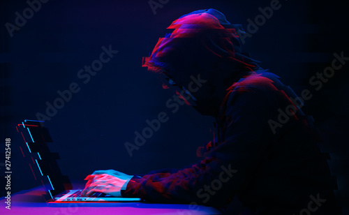 Tela Hacker in the hood working with laptop typing text in dark room