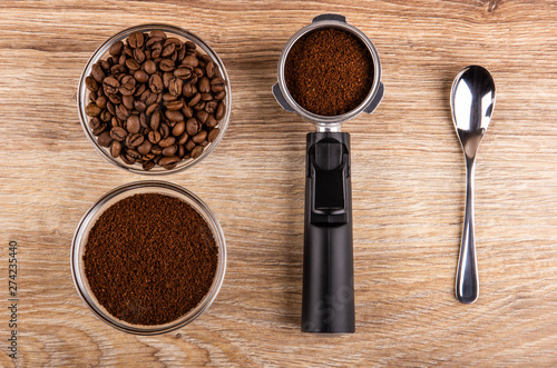 Fototapeta Bowl with coffee beans, holder from coffeemaker with ground coffee, bowl with ground coffee, spoon on table