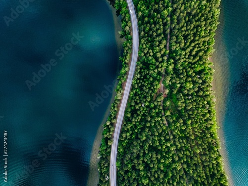 Fotografia Aerial view of road between green forest and blue lake in Finland