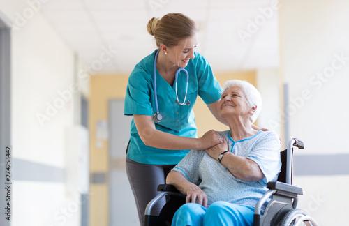 Fotografie, Obraz Senior woman in wheelchair with nurse in hospital