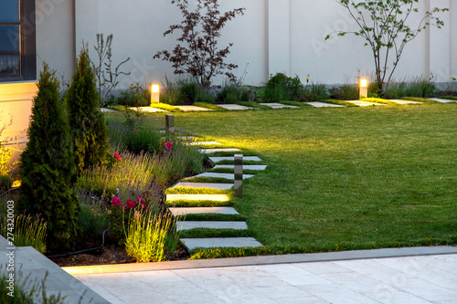Valokuva backyard of the mansion with a flowerbed and a lawn of green grass with a marble walkway of square tiles in the evening with a garden lighting with decorative ground lamps illuminating a warm light