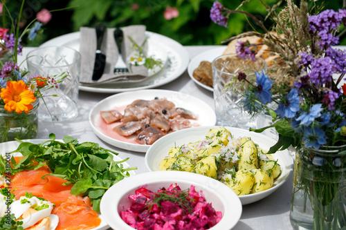 Fototapeta Scandinavian midsummer feast with potato salad, herring, salmon and beetroot