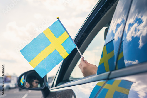 Wallpaper Mural Woman or Girl Holding Swedish Flag from the open car window