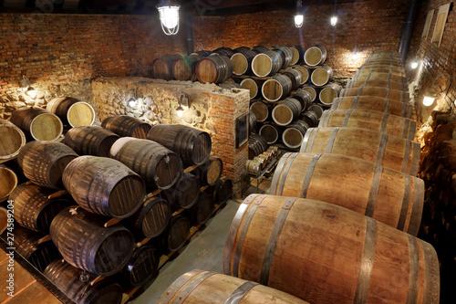Fotografia Rows of alcoholic barrels are kept in stock