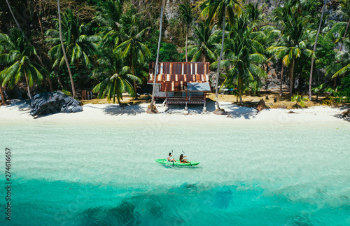 Canvas Print Couple enjoying time kayaking in front of the beach in Coron