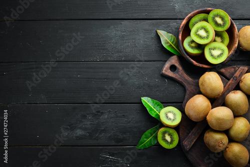 Fotografia Fresh kiwi and green leaves on the table