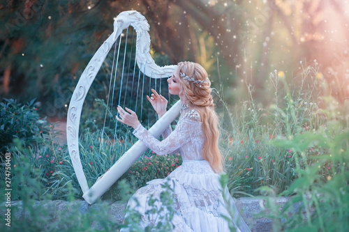 Canvas Print mysterious forest nymph plays on white harp in fabulous place, girl with long blond hair and elegant lace vintage dress calling for bright sun rays, lady with silver jewelry and musical instrument