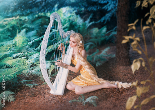 Valokuvatapetti fabulous forest elf sits under tree and plays on white harp, girl with long blond hair braided in long yellow dress, summer goddess rests and sings to the sound of a magical musical instrument