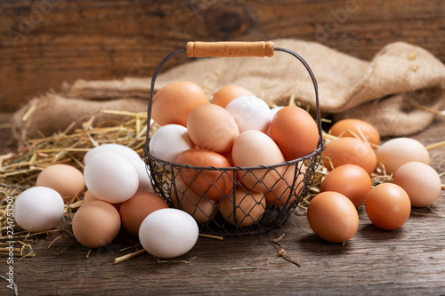 Photo basket of colorful fresh eggs on wooden table