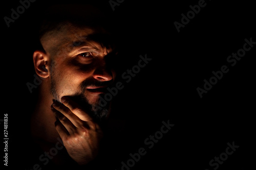 Fotografia, Obraz Face with a bearded man grimace against a dark background with sharp shadows