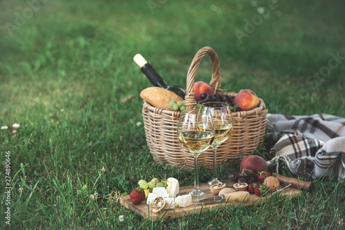 Fotografia Picnic setting with  white wine,  cheese, fruits and nuts