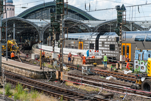 Fototapeta Regional train incoming in station in Cologne / Germany while workers build new