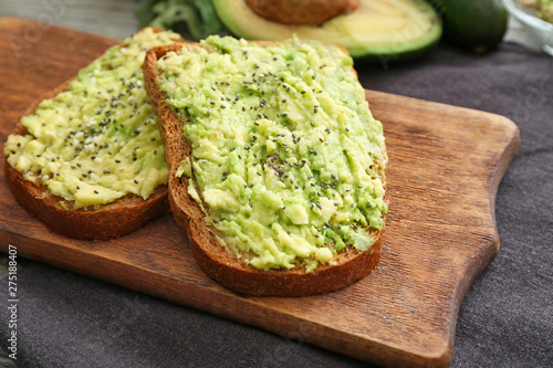 Платно Tasty avocado toasts on wooden board